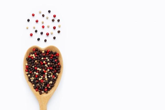 Granelli di pepe neri, rossi e bianchi con il cucchiaio di legno su bianco