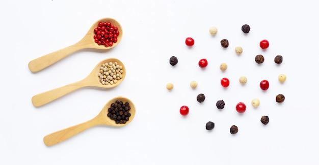 Granelli di pepe rossi, bianchi e neri con il cucchiaio di legno su bianco