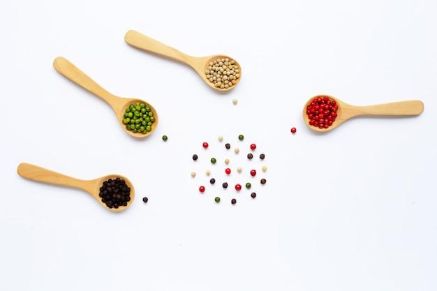 Granelli di pepe rossi, verdi, bianchi e neri con il cucchiaio di legno su bianco.