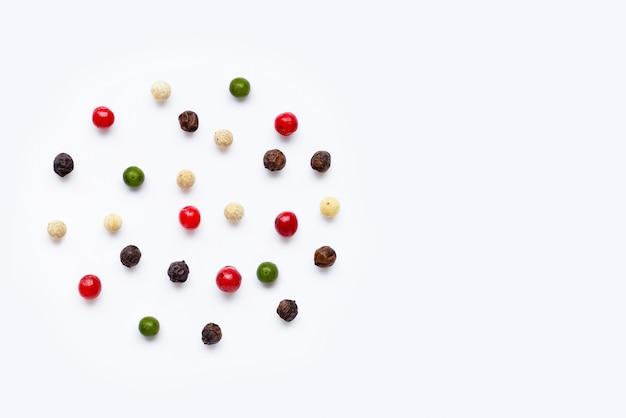 Granelli di pepe rossi, verdi, bianchi e neri su bianco