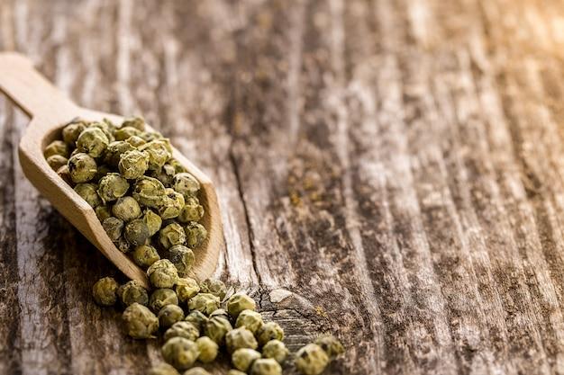 Granelli di pepe verdi in un cucchiaio sulla tavola di legno