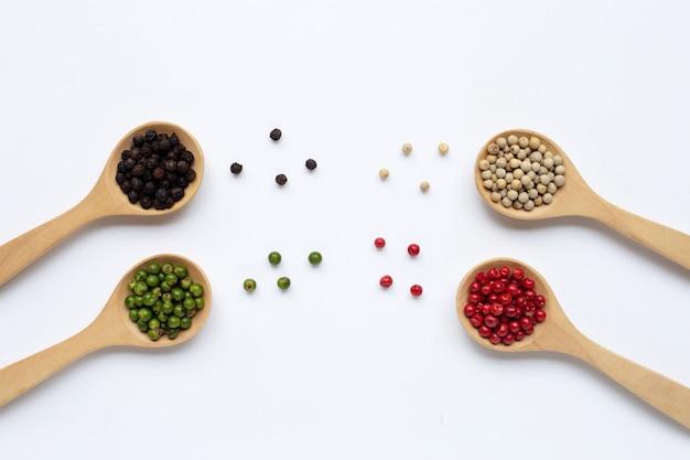 Granelli di pepe verdi, rossi, bianchi e neri con il cucchiaio di legno su bianco