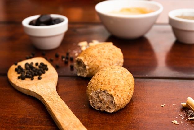 Granello di pepe nero sulla spatola di legno con pane sopra la tavola marrone