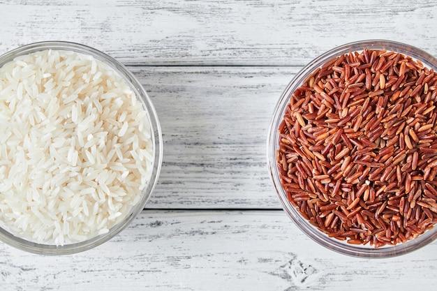 Grani crudi del riso rosso e bianco in una lastra di vetro trasparente su fondo di legno.