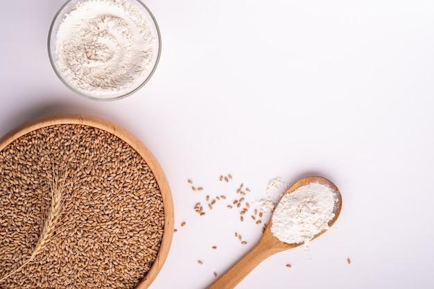 Grani dei semi di grano in ciotola di legno, farina di frumento in ciotola di vetro
