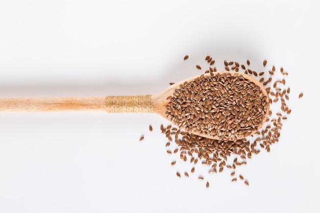 Grani di lino, spezie in un cucchiaio di legno su un bianco. , copyspace.