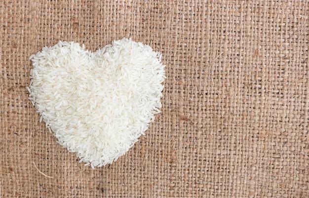 Grani di riso a forma di cuore su vecchio fondo del sacco. sopra la luce