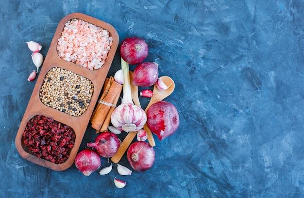 Grani e spezie in un piatto di legno con bastoncini di cannella, cucchiai, aglio, vista dall'alto di cipolle rosse su sfondo blu grunge
