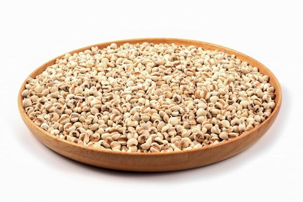 Grani organici del miglio sul piatto di legno marrone su bianco