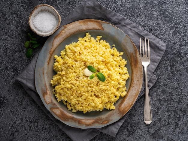 Grano bulgur. cereale bollito del bulghur in piatto sul tavolo di pietra grigio scuro. cibo vegetariano sano