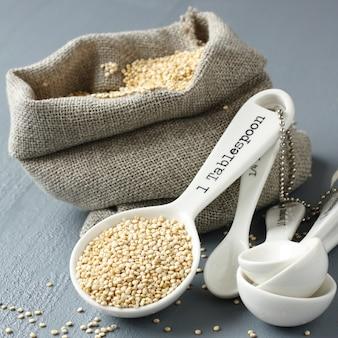 Grano di quinoa in un piccolo sacco di iuta e porcellana che misura i cucchiai su sfondo grigio