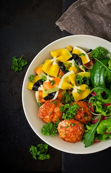 Grano duro di farfalle con polpette al forno di filetto di pollo in salsa di pomodoro e insalata in ciotola.