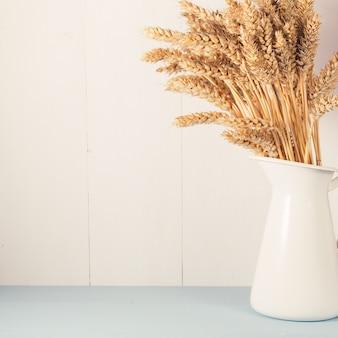 Grano maturo in vaso bianco su fondo di legno