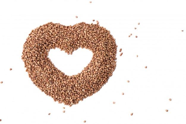 Grano saraceno a forma di cuore isolato su sfondo. amore per il porridge di grano saraceno. semole di grano saraceno, semi. vista dall'alto.