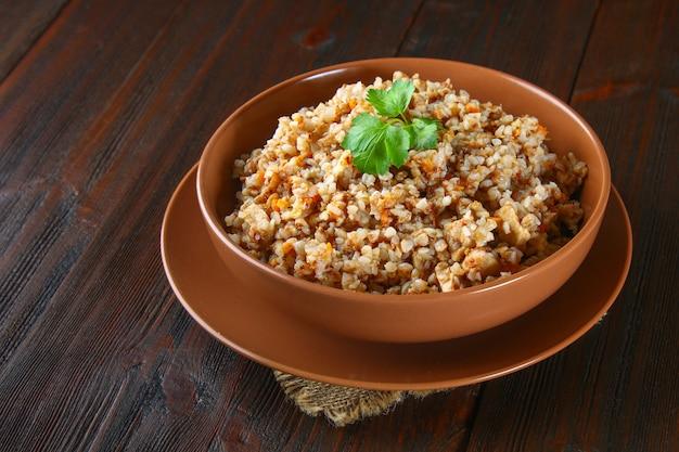 Grano saraceno bollito in una ciotola con pezzi di carne di pollo e coriandolo su un tavolo di legno marrone.