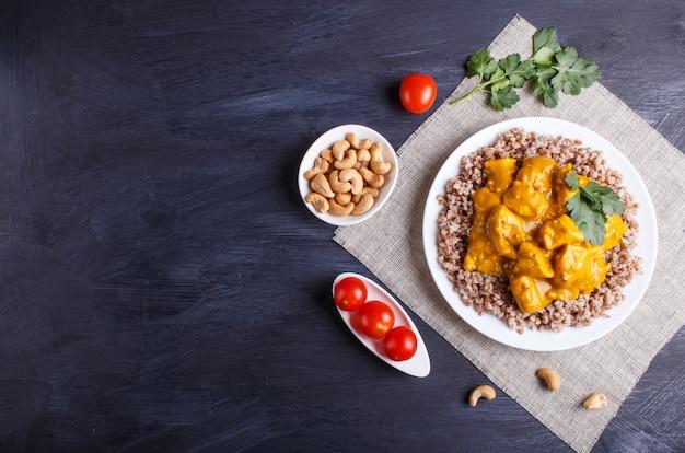 Grano saraceno con salsa al curry di pollo con anacardi su superficie in legno nero.