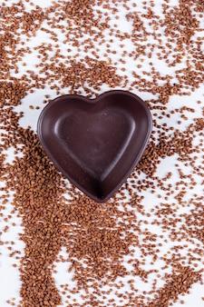 Grano saraceno con vista dall'alto di ciotola vuota a forma di cuore su un bianco