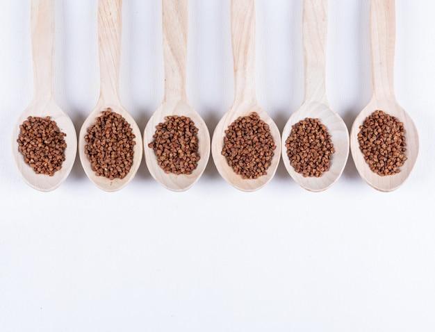 Grano saraceno in cucchiai di legno su un bianco. vista dall'alto. spazio per il testo