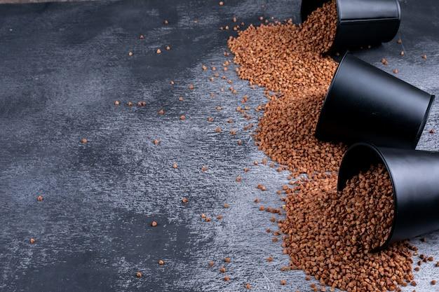 Grano saraceno in secchi su un grigio scuro. veduta dall'alto. spazio per il testo