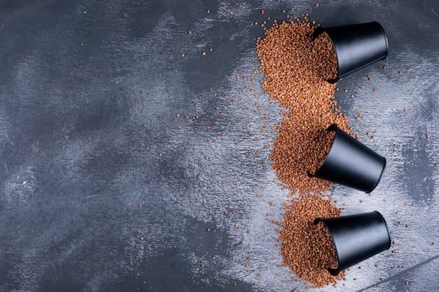 Grano saraceno in secchi su un grigio scuro. vista dall'alto. spazio per il testo