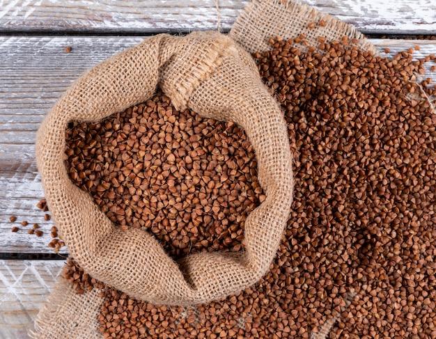 Grano saraceno in un sacco su un panno di sacco e legno chiaro. disteso.