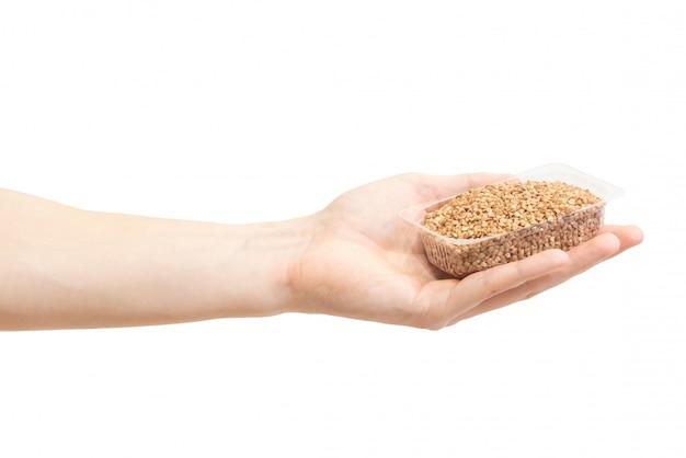 Grano saraceno marrone crudo in contenitore di plastica trasparente in mano maschile