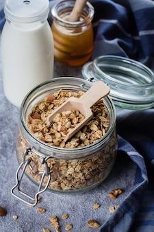 Granola casalingo in vaso di vetro sul tavolo di pietra grigia. ingredienti per una sana colazione