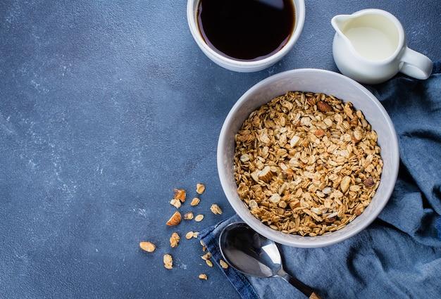 Granola della prima colazione, latte o yogurt e miele sul vassoio di legno sul fondo di pietra della tavola. vista dall'alto
