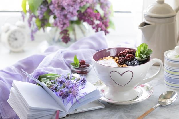Granola di casa con frutti di bosco sul tavolo vicino alla finestra con un mazzo di lillà.