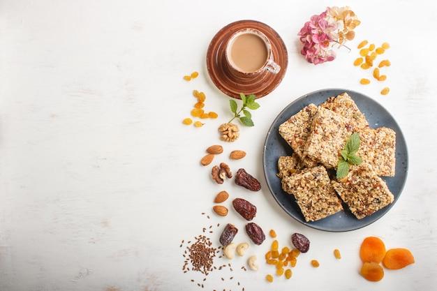 Granola fatta in casa da fiocchi d'avena, datteri, albicocche secche, uvetta, noci in un piatto di ceramica blu. vista dall'alto.