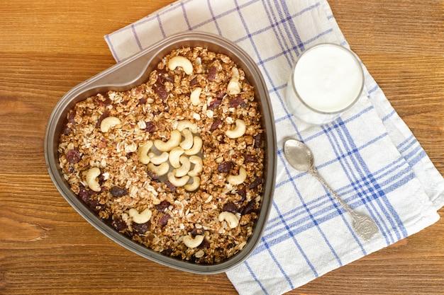 Granola su una teglia e yogurt su un tavolo di legno.