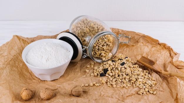 Granola versato dal barattolo; farina; noci su carta stropicciata marrone