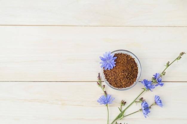 Granuli liofilizzati istantanei dalla radice di cicoria su un tavolo di legno chiaro. fiori blu freschi cichorium intybus. sostituto naturale del caffè.