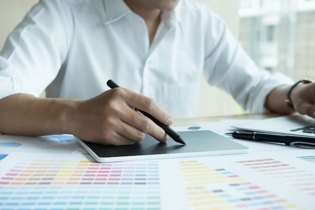 Graphic designer che lavora con computer e campioni di colore
