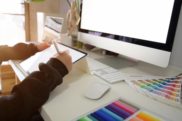 Graphic designer che lavora con tablet in un ambiente di lavoro creativo