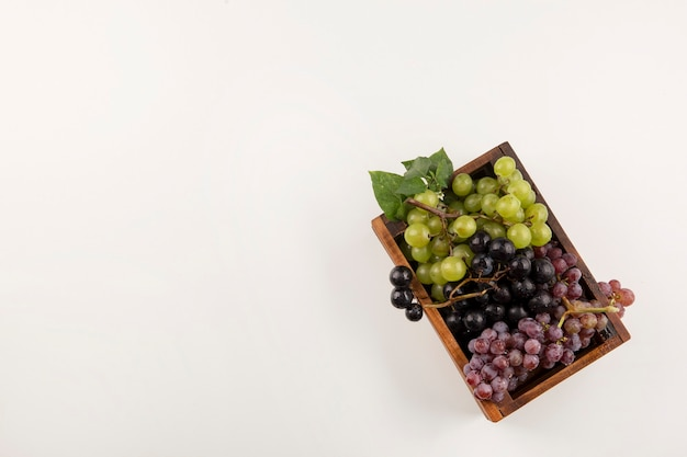 Grappoli d'uva verdi e rossi in una scatola di legno nella parte inferiore