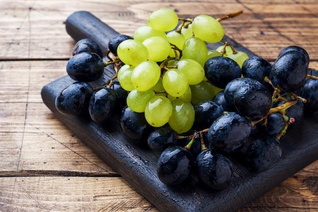 Grappoli di uva nera e verde kish mish su una tavola di legno. copyspace.