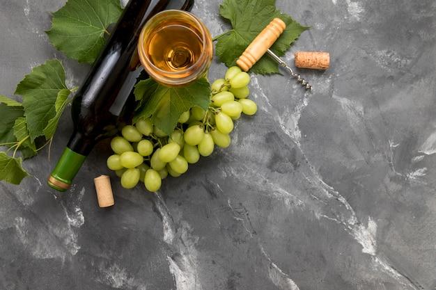 Grappolo d'uva con bottiglia di vino su sfondo di marmo