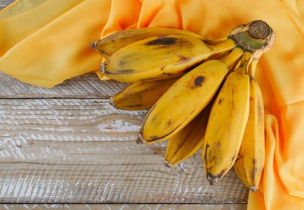 Grappolo di banana su legno e tessuto.