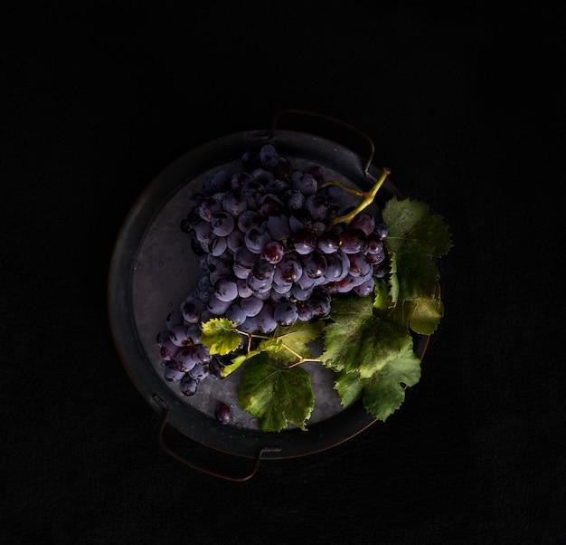 Grappolo scuro di uva con gocce d'acqua in condizioni di scarsa luminosità