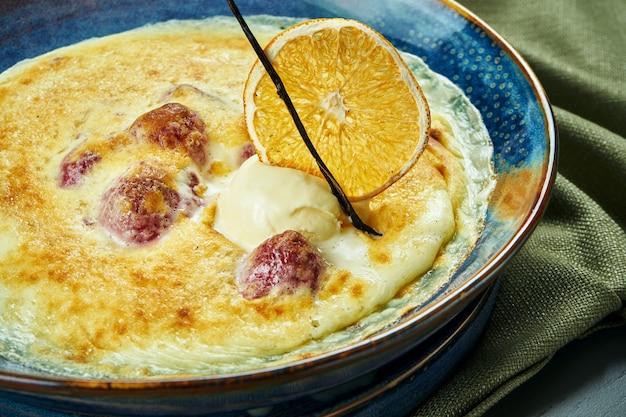 Gratin della bacca con il gelato in una ciotola blu sulla tavola di legno. dessert cotto francese saporito e dolce. primo piano, messa a fuoco selettiva