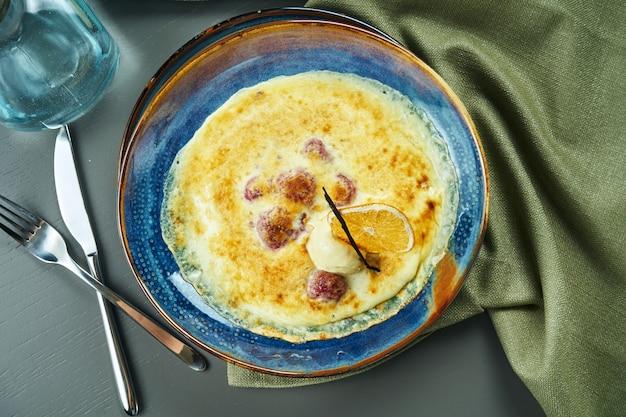 Gratin della bacca con il gelato in una ciotola blu sulla tavola di legno. dessert cotto francese saporito e dolce. vista dall'alto, piatto, composizione centrale