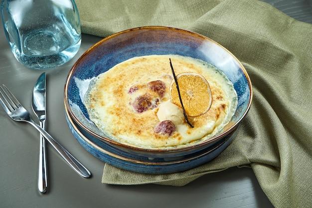 Gratin della bacca con il gelato in una ciotola blu sulla tavola di legno. dessert cotto francese saporito e dolce