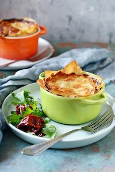 Gratin di patate al forno in pasta fillo, con crosta di formaggio croccante e insalata di rucola, pomodori secchi e formaggio su una parete blu. un piatto di cucina francese