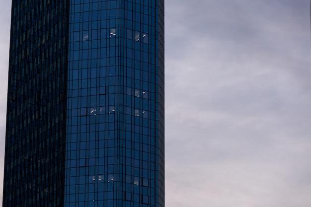 Grattacielo in una facciata di vetro sotto il cielo nuvoloso a francoforte, germania