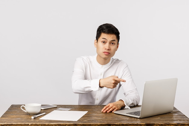 Grave dispiaciuto giovane imprenditore asiatico seduto alla scrivania, indicando lo schermo del laptop e guardando severo, accigliato scettico, rimprovero dipendente fatto cattivo rapporto, lavorando