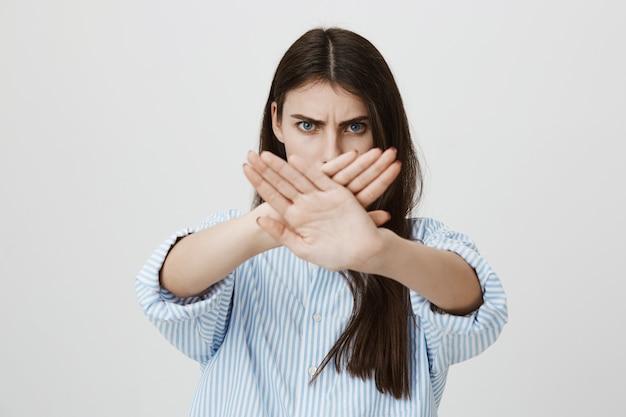Grave donna sicura di sé visualizza segnale di stop, gesto trasversale