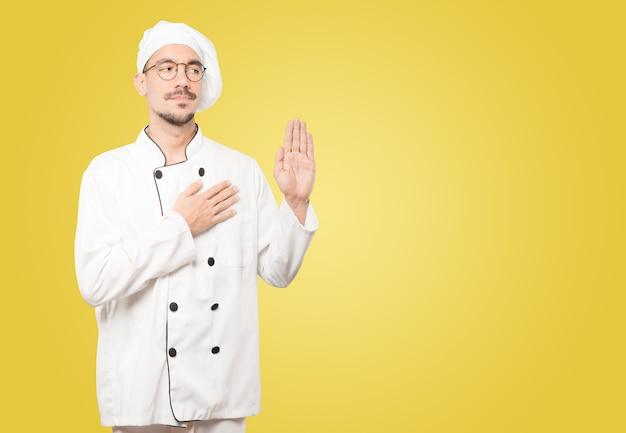 Grave giovane chef con un gesto di giuramento