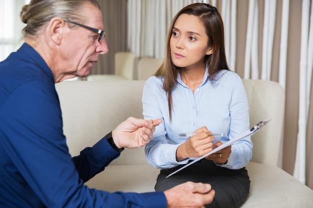 Grave giovane donna che intervista un uomo anziano