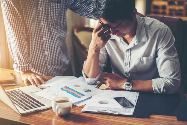 Grave giovane imprenditore guardando relazione finanziaria sembrare